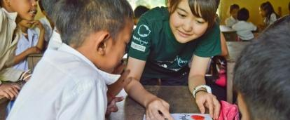 Children are taught by female volunteers working with children in Cambodia inside a community care centre to further their childhood development.